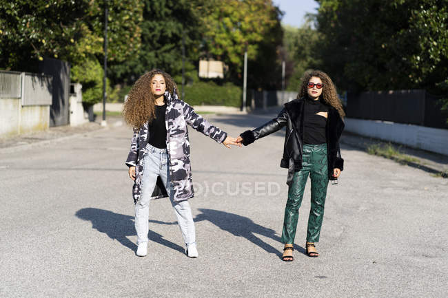 Portrait of fashionable twin sisters holding hands — Stock Photo