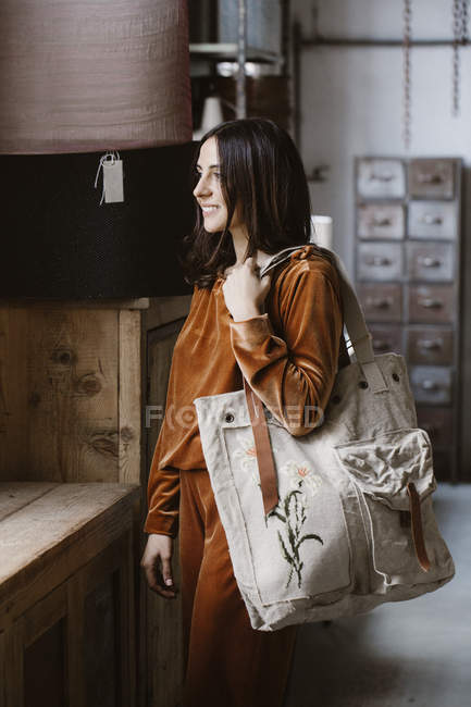 Sonriente mujer joven de moda con gran bolsa de compras en un loft - foto de stock