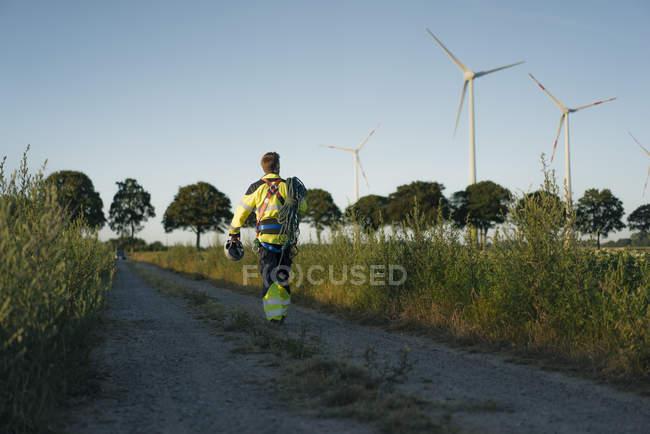 Техник, идущий по полевой дорожке на ветропарке с альпинистского снаряжением — стоковое фото