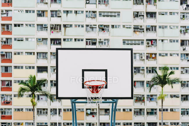 China, Hong Kong, Kowloon, basketball hoop, public housing in the background — Stock Photo