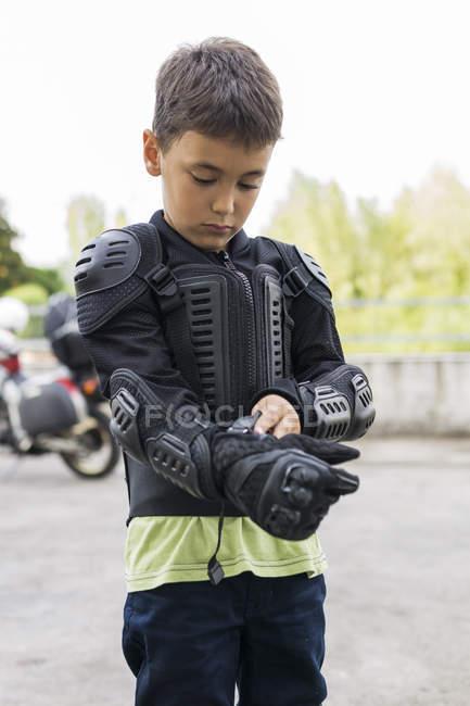 Garçon portant des vêtements de protection se préparant pour un voyage à moto — Photo de stock