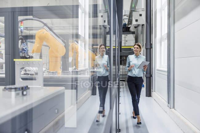 Mulher de negócios que verific robôs com a tabuleta digital na companhia alta tecnologia — Fotografia de Stock