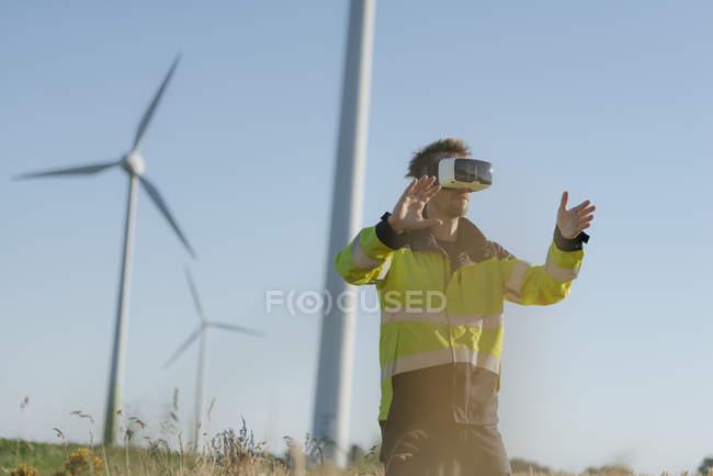 Инженер, стоящий в поле на ветряной электростанции и носящий очки VR — стоковое фото