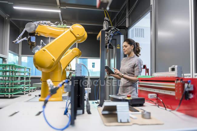 Mulher de negócios que verific o robô industrial na companhia alta tecnologia — Fotografia de Stock