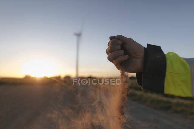 Close-up of man scattering soil at a wind turbine at sunset — Stock Photo