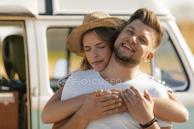 Happy affectionate young couple at camper van — Stock Photo