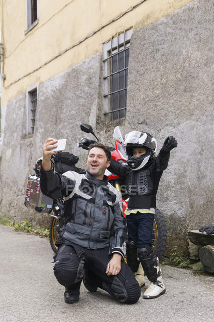 Happy father and son taking a selfie on a motorbike trip — Stock Photo