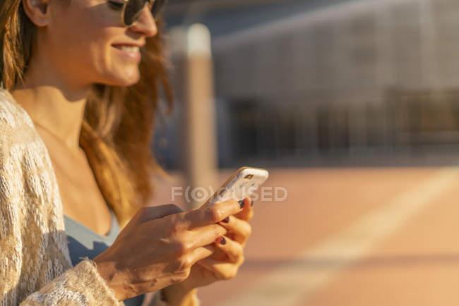 Sorrindo jovem mulher com telefone celular ao ar livre — Fotografia de Stock