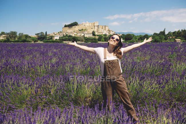 Франция, Гриньян, счастливая женщина, стоящая на лавандовом поле — стоковое фото