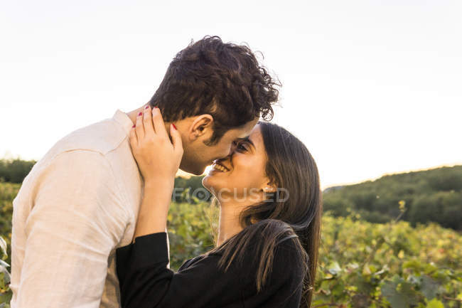 Italy, Tuscany, Siena, happy young couple kissing in a vineyard — Stock Photo