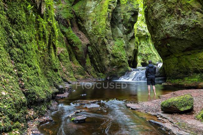 Gran Bretagna, Scozia, Trossachs National Park, Finnich Glen canyon, turista maschio in piedi in acqua — Foto stock