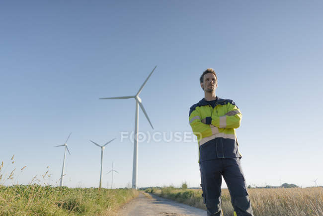 Engineer standing on field path at a wind farm — Stock Photo
