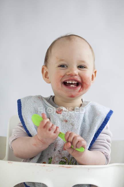 Портрет щасливої дівчинки з гладеньким обличчям на високому стільці. — стокове фото
