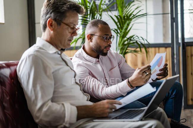 Zwei Geschäftsleute nutzen Laptop und diskutieren Dokumente auf Sofa im Loft-Büro — Stockfoto