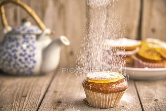 Sprinkling icing sugar on muffin with candied orange on top — Stock Photo
