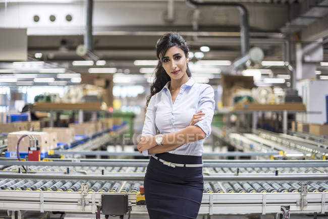 Portrait of confident woman at conveyor belt in factory — Stock Photo