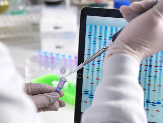 Scientifique pipettant un échantillon d'ADN avec les résultats sur une scéne informatique dans un laboratoire — Photo de stock