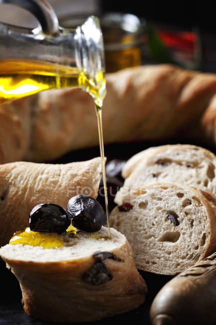 Pouring olive oil on slice of ring bread with black olives — Stock Photo