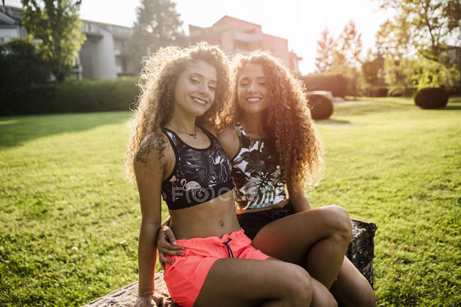 Portrait of smiling twin sisters at backlight — Stock Photo