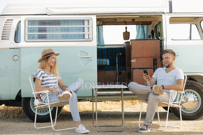 Happy young couple sitting on camping chairs at camper van with cell phone — Stock Photo