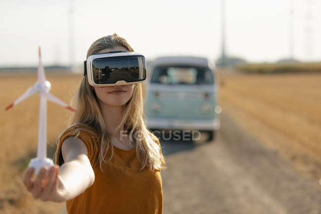 Young woman with VR glasses at camper van in rural landscape holding wind turbine model — Stock Photo