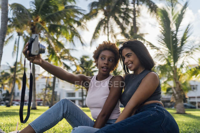 Two happy female friends taking an instant photo in a park — стоковое фото