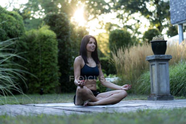 Woman practicing yoga in garden — Stock Photo