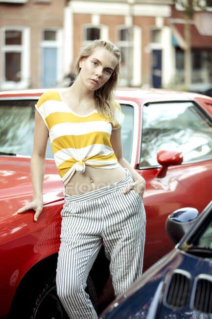 Retrato de la joven que se apoya en el coche vintage rojo - foto de stock