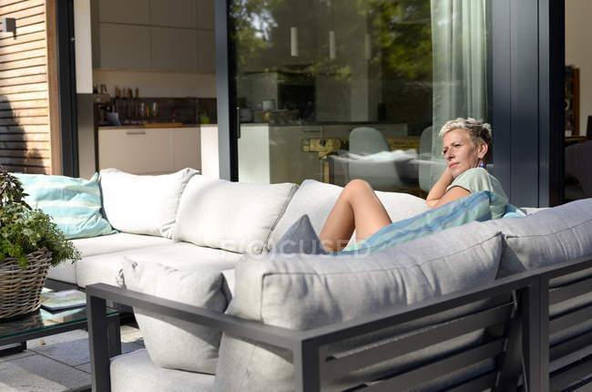 Nachdenkliche Frau sitzt auf Couch auf der Terrasse ihres Hauses — Stockfoto