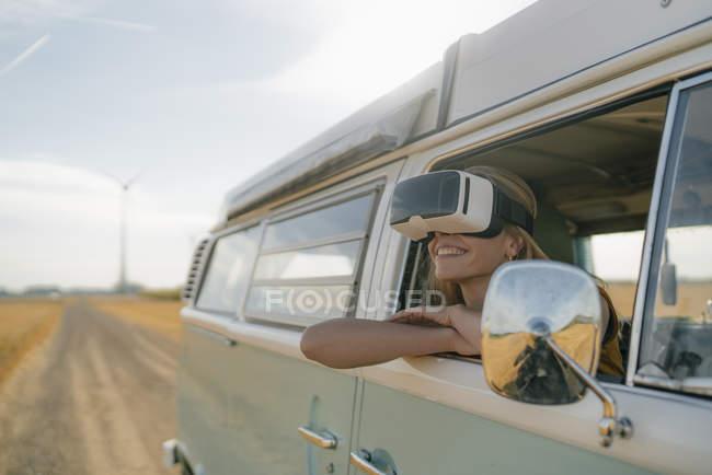 Улыбающаяся женщина в очках от виртуальной реальности, высунутая из окна фургона — стоковое фото