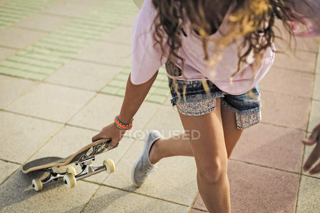 Girl with skateboard, copy space — Stock Photo