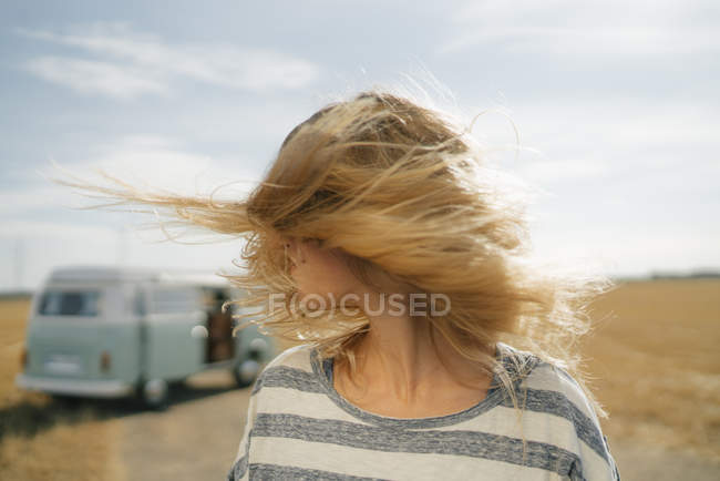 Blonde young woman at camper van in rural landscape shaking her hair — Stock Photo