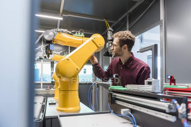 Homem de negócios que verific o robô industrial na companhia alta tecnologia — Fotografia de Stock