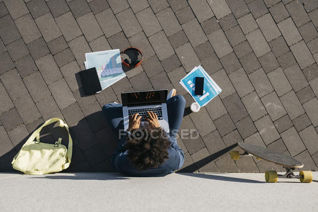 Young businessman sitting outdoors at a wall and working on laptop — Stock Photo