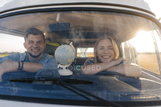 Portrait of happy young couple on a trip in camper van — Stock Photo