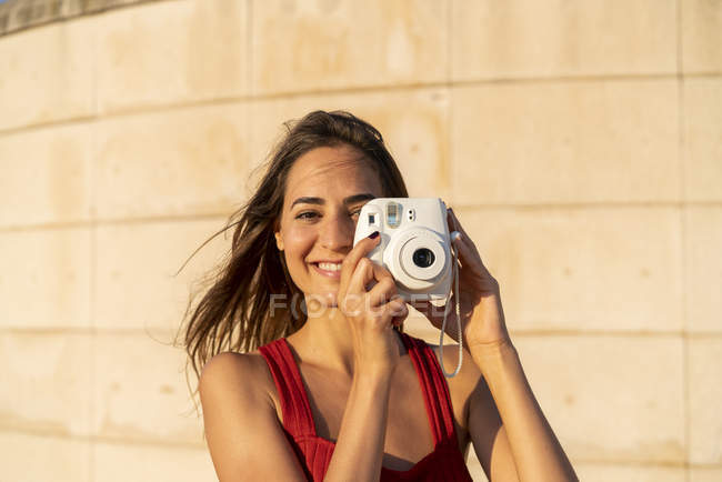 Portrait of smiling young woman taking instant photo outdoors — Stock Photo