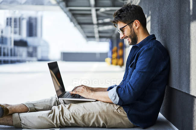 Sonriente joven sentado en el suelo usando un ordenador portátil - foto de stock