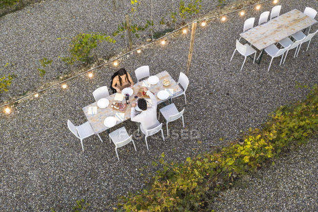 Italy, Tuscany, Siena, top view of young couple having dinner in a vineyard — Foto stock