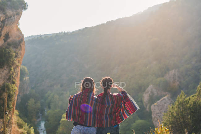 Spain, Alquezar, rear view of two young women on a hiking trip sharing a blanket — Stock Photo