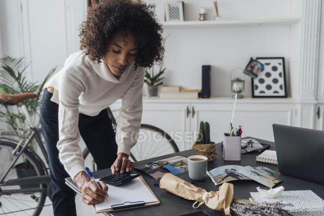 Freelancer debout au bureau de hert, utilisant le calculateur, prenant des notes — Photo de stock