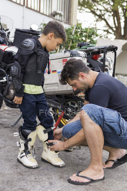 Father preparing son for a motorbike trip — Stock Photo