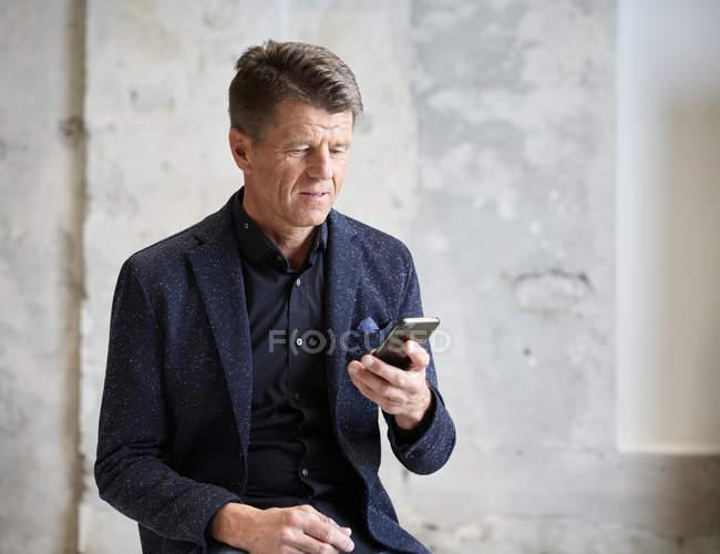 Homme d'affaires regardant le téléphone portable — Photo de stock