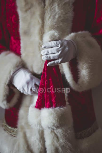 Hand of Santa Claus holding Christmas cap — Stock Photo