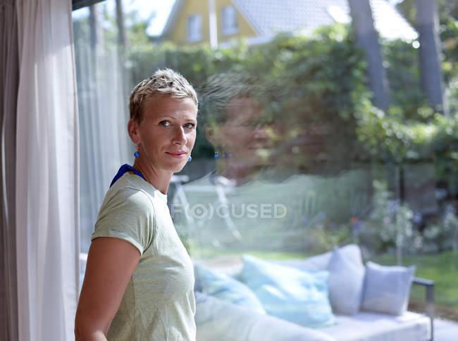 Porträt einer Frau mit kurzen Haaren, die zu Hause vor dem Fenster steht — Stockfoto