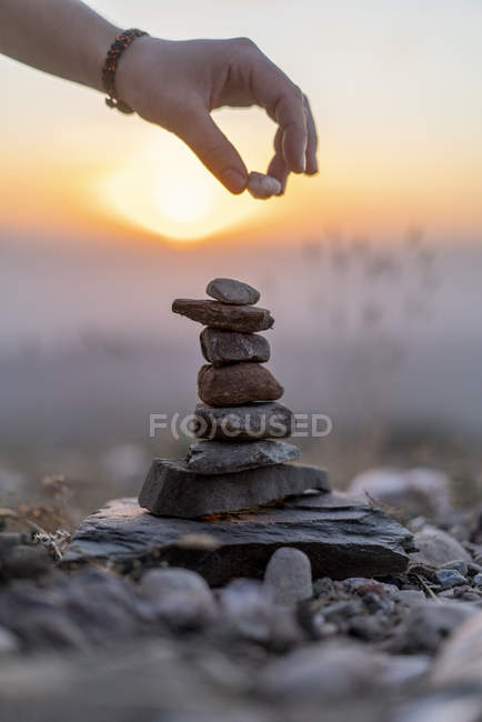 Close-up of male hand placing stone on cairn at sunset — Fotografia de Stock