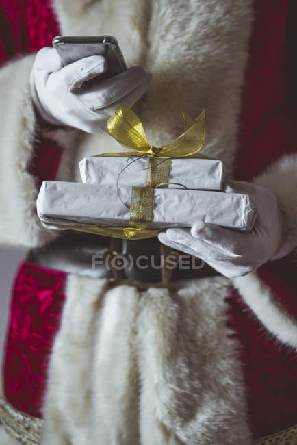 Санта Клаус зі смартфоном і різдвяними подарунками. — стокове фото