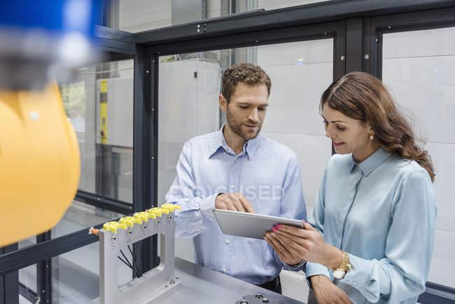 Colegas na empresa de alta tecnologia controlando máquinas de fabricação, usando tablet digital — Fotografia de Stock