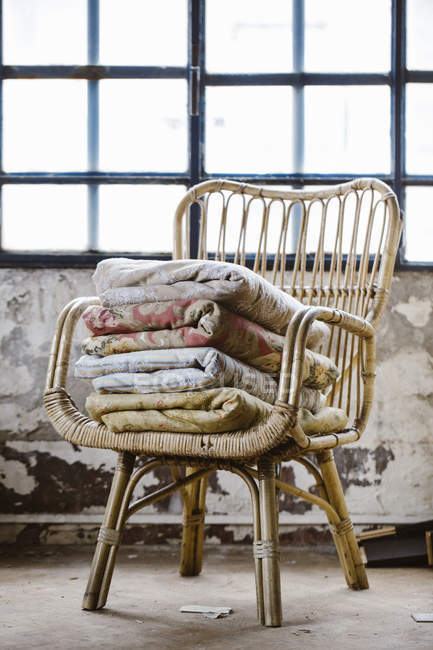 Stack of various blankets on basket-chair in a loft — Stock Photo