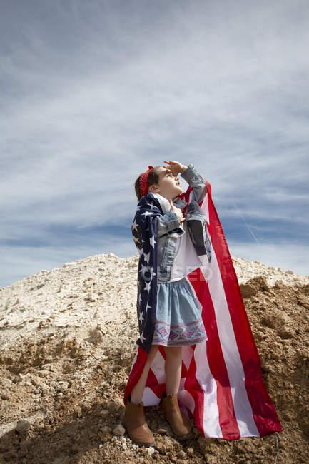 Девочка, стоящая на раскаленном грунте с американским флагом — стоковое фото