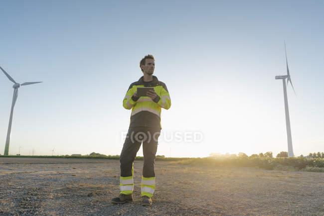 Ingenieur steht in ländlicher Landschaft an einem Windpark und hält Tablet — Stockfoto